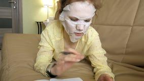 De jonge vrouw die gezichtsmaskermasker met het reinigen van masker doen, klikt thuis op laag met smartphone royalty-vrije stock foto's