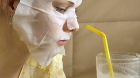 De jonge vrouw die gezichtsmaskermasker met het reinigen van masker doen, klikt thuis op laag met smartphone royalty-vrije stock fotografie