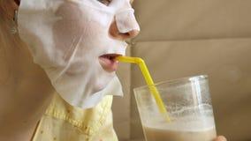 De jonge vrouw die gezichtsmaskermasker met het reinigen van masker doen, klikt thuis op laag met smartphone royalty-vrije stock afbeeldingen