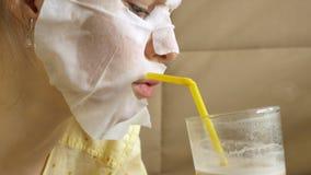 De jonge vrouw die gezichtsmaskermasker met het reinigen van masker doen, klikt thuis op laag met smartphone stock foto