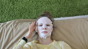 De jonge vrouw die gezichtsmaskermasker met het reinigen van masker doen, klikt thuis op laag met smartphone stock fotografie