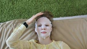 De jonge vrouw die gezichtsmaskermasker met het reinigen van masker doen, klikt thuis op laag met smartphone royalty-vrije stock afbeelding