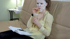 De jonge vrouw die gezichtsmaskermasker met het reinigen van masker doen, klikt thuis op laag met smartphone stock afbeeldingen