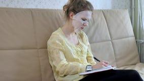De jonge vrouw die gezichtsmaskermasker met het reinigen van masker doen, klikt thuis op laag met smartphone stock afbeelding