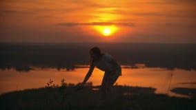 De jonge vrouw die het kind roepen om te spelen badminton op de heuvel bij suddert zonsondergang stock videobeelden