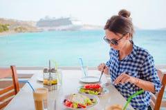 De jonge vrouw die lunch met heerlijke verse Griekse salade, frappe en brusketa hebben diende voor lunch bij openluchtrestaurant stock afbeelding