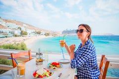 De jonge vrouw die lunch met heerlijke verse Griekse salade, frappe en brusketa hebben diende voor lunch bij openluchtrestaurant stock foto