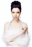 De jonge vrouw die op witte studioachtergrond wordt geïsoleerd kleedde zich in de kaap van organza Royalty-vrije Stock Afbeelding