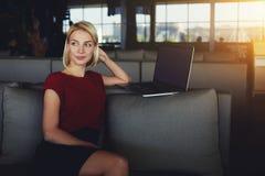De jonge vrouw die over nieuwe ideeën denken voor creeert een plaatsontwerp op laptop computer terwijl het zitten in modern binne stock foto