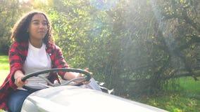 De jonge vrouw die van de Biracialtiener een grijze tractor drijven door een zonnige appelboomgaard stock video