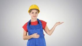 De jonge vrouw die van de bouwersarbeider tonend product met haar handen van haar kanten op gradiëntachtergrond voorstellen stock afbeelding