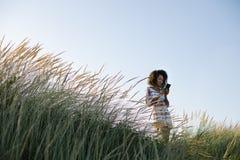 De jonge vrouw die van het afrohaar smartphone in aard gebruiken bij het strand stock foto's