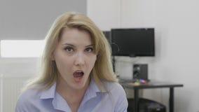 De jonge vrouw die van het blondebureau op het werk omg oh zeggen mijn Godsreactie met verbaasd gezicht en geopende mond - stock video