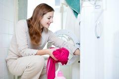 De jonge vrouw die van het huishoudelijk werk wasserij doet Stock Foto