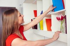 Vrouw die boek van de plank krijgen royalty-vrije stock afbeeldingen