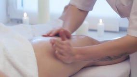 De jonge vrouw die voetenmassage in beauty spa salon hebben, sluit omhoog De masseur kneedt de voet en het been van een jong mooi stock video