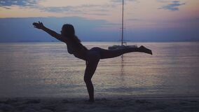 De jonge vrouw die yoga, het doen uitoefenen stelt op strand tijdens mooie zonsondergang Langzame Motie 1920x1080 stock footage
