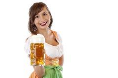 De jonge vrouw in dirndl houdt meest oktoberfest bierstenen bierkroes stock foto's