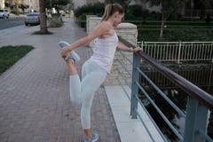 De jonge vrouw doet het stratching na de looppas stock fotografie
