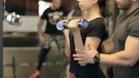 De jonge vrouw doet de krullen van de bicepsendomoor met trainer in sportclub stock footage