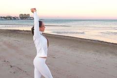 De jonge vrouw doet oefeningen ademhaling op het zandstrand bij zonsopgang in de herfst, achtermening herstellen royalty-vrije stock foto