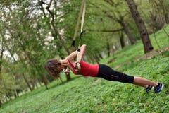De jonge vrouw doet opschorting opleiding met geschiktheidsriemen in stock afbeelding
