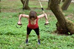 De jonge vrouw doet opschorting opleiding met geschiktheidsriemen in stock foto