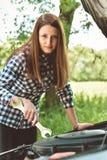De jonge vrouw door de kant van de weg na haar auto heeft opgesplitst Gestemd beeld Royalty-vrije Stock Afbeeldingen