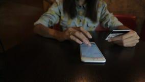 De jonge vrouw draait of typt het krediet of het aantal van de debetkaart het proberen bewaart het in smartphone stock videobeelden