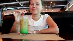 De jonge vrouw drinkt een cocktail stock video