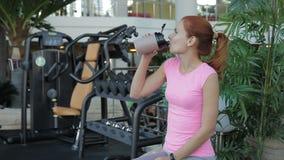 De jonge vrouw drinkt eiwitcocktail terwijl het zitten in gymnastiek stock videobeelden