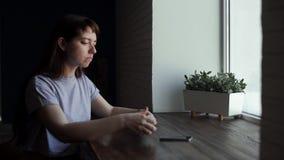 De jonge vrouw drinkt koffie bij koffie, maakt slokje en kijkt aan venster stock footage