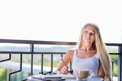 De jonge vrouw drinkt koffie en het schrijven in het dagboek van het notaboek in caf stock foto's