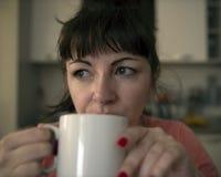 De jonge vrouw drinkt koffie in de ochtend in de keuken, vermoeide ogen met rode aders, close-up stock foto
