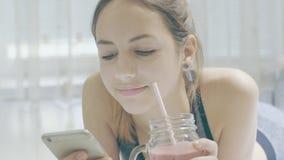 De jonge vrouw drinkt smoothies en gebruikt een geschiktheid app op haar smartphone stock video