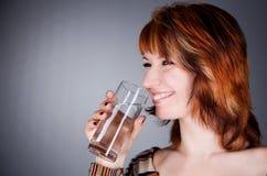 de jonge vrouw drinkt water Stock Afbeelding