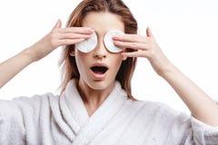 De jonge vrouw in een badjas maakt het gezicht met katoenen stootkussens, kuuroord en zorgportret schoon, schoon natuurlijk gezic stock fotografie