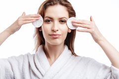 De jonge vrouw in een badjas maakt het gezicht met katoenen stootkussens, kuuroord en zorgportret schoon, schoon natuurlijk gezic stock foto