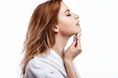 De jonge vrouw in een badjas maakt het gezicht met katoenen stootkussens, kuuroord en zorgportret schoon, schoon natuurlijk gezic royalty-vrije stock fotografie