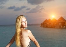 De jonge vrouw in een badpak bij zonsondergang op achtergrond van het overzees en de silhouetten van huizen over water stock foto's