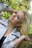 De jonge vrouw een blonde glimlacht op achtergrondbomen Stock Foto's