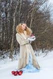 De jonge vrouw in een bontjas stelt bij de winterbos Royalty-vrije Stock Afbeelding