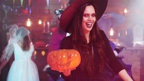 De jonge vrouw in een heksenkostuums maakt een kwade lach die gesneden houden pumpkun stock video