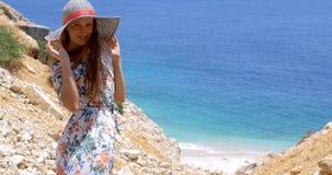 De jonge vrouw in een hoed bekijkt het azuurblauwe overzees stock videobeelden