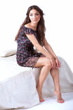De jonge vrouw in een kleding zit op rand van het bed royalty-vrije stock foto
