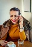 De jonge vrouw in een koffie drinkt koffie en het spreken op smartphone stock afbeeldingen