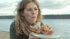 De jonge vrouw in een laag zit op het strand door de rivier, oceaan, heeft een picknick, eet een hamburger in aard, koud weer stock footage