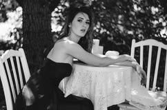 De jonge vrouw in een lange avondjurk zit bij een lijst in het hout Zwart-witte fotografie Stock Afbeeldingen