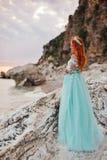 De jonge vrouw in een luxueuze kleding bevindt zich op de kust van het Adriatische Overzees royalty-vrije stock afbeelding