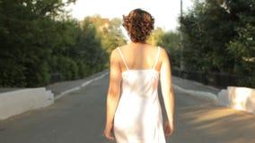 De jonge vrouw in een nachtjapon gaat op de weg, achtermening stock videobeelden